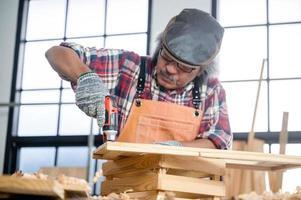 Carpintero profesional hombre que trabaja con la herramienta de la industria de la carpintería, taller de persona artesano con madera y equipos de construcción de carpintería foto