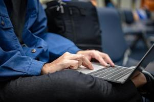 Businessman sitting and using a laptop computer to work at the airport, young person traveling, journey and having internet communication technology for work when waiting indoors at an airport for departure photo