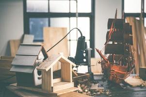 Imagen de fondo del taller de carpintería: mesa de trabajo de carpinteros con diferentes herramientas y soporte de corte de madera, imagen de filtro vintage foto