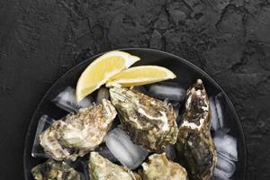 Top view plate with oysters and lemon slices photo