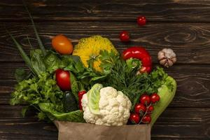 Top view vegetables on wooden background photo