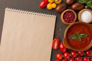 Top view winter tomato soup bowl with notebook photo