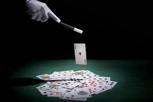 Magician performing trick playing cards with magic wand poker table photo