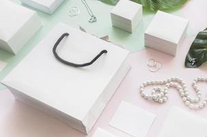 Bolsas de compras blancas y cajas de regalo con joyas sobre fondo de color foto