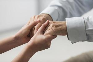 enfermera sosteniendo las manos del hombre mayor con simpatía foto