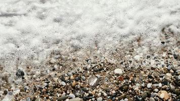 Pebbles with waves coming in photo