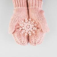 Persons hands in mittens with paper snowflake photo