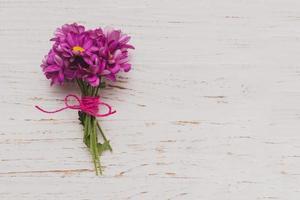 Flores moradas atadas a la superficie de madera blanca. concepto de fotografía hermosa de alta calidad y resolución foto