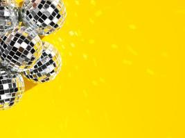 Set of bright disco globes with copy space on yellow background photo