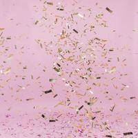 Shiny golden confetti falling on pink background photo