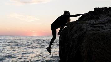 Sideways silhouetted woman climbing rock near water photo