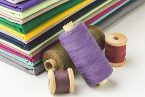 Stack of fabric with spools of thread photo