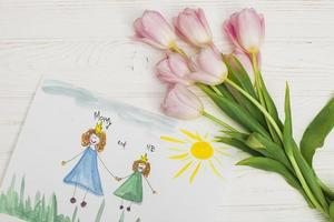 A kids drawing of mother and daughter with flower photo