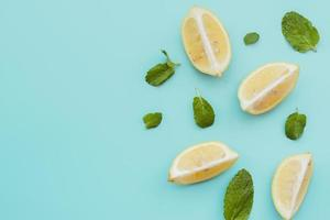 rodajas de limón y fondo de hojas de menta foto