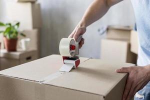 Hombre usando cinta adhesiva en una caja lista para mudarse foto