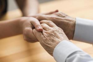 Enfermera sosteniendo las manos del hombre mayor con empatía foto