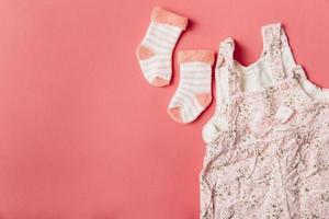 Par de calcetines de bebé y vestido sobre fondo de color brillante foto