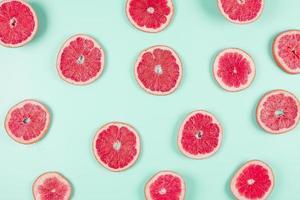 Pattern of grapefruit citrus slices on pastel backdrop photo