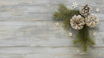 Pine needles on wooden background with conifer cones photo