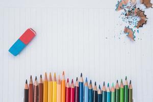 Fila de colores de lápiz con goma de borrar y virutas de lápiz sobre papel blanco foto