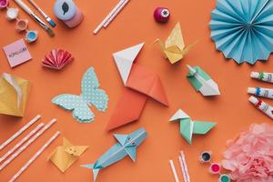 Set of origami paper art and paint brush with watercolor and straws on orange backdrop photo