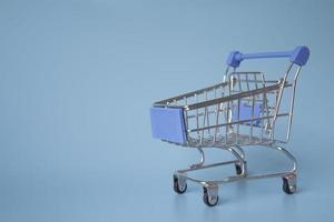 Miniature shopping cart on blue background photo