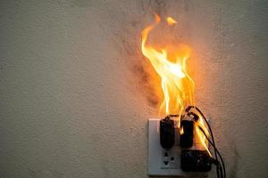 Power plug adapter on fire, electric short circuit failure resulting in electricity wire burning photo