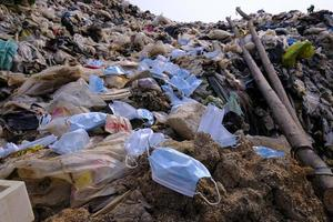 Discarded used medical face masks along among garbage, trash with other plastic debris lies on the ground photo