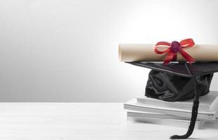 Certificado de graduación y gorra sobre fondo blanco. foto