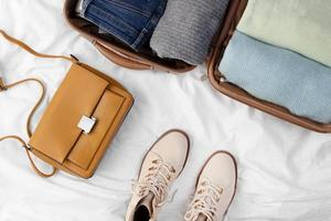 Opened luggage with folded clothes and shoes photo