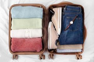equipaje abierto con ropa y zapatos doblados foto