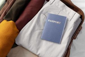 Opened luggage with folded clothes and passport photo