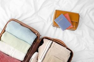 Opened luggage with folded clothes and passports photo