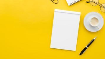 Vista superior del cuaderno en blanco sobre fondo amarillo foto