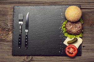 Vista superior de los ingredientes de la hamburguesa en tablero de pizarra foto
