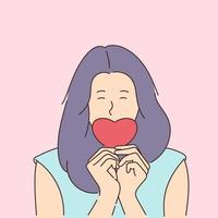 Love story or Valentines day concept. Young smiling girl covers her mouth with a paper red heart. vector
