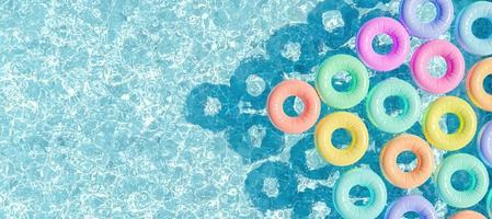 Swimming pool seen from above with many rings floating, 3d render photo