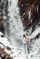 Bride and groom on the mountain waterfall photo