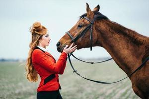 jockey pelirroja con un cárdigan rojo y botas altas negras con un caballo foto