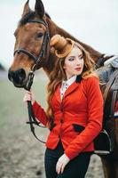Red-haired jockey girl in a red cardigan and black high boots with a horse photo