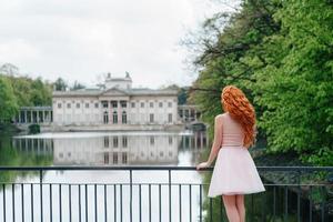 Joven pelirroja caminando en un parque entre árboles y objetos arquitectónicos foto
