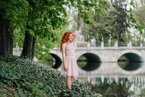 Joven pelirroja caminando en un parque entre árboles foto