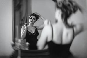 Young brunette model girl and actress in front of a mirror photo