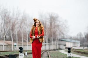 Young girl with red hair in a bright red dress on the railway tracks photo