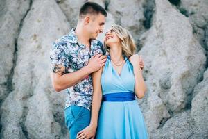 Blonde girl in a light blue dress and a guy in a light shirt in a granite quarry photo