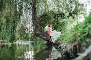 un chico y una chica están sentados juntos en un árbol torcido en la orilla empinada foto