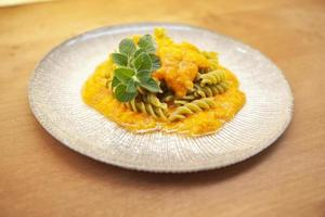 Plate of fusilli with pea flour in pepper sauce photo