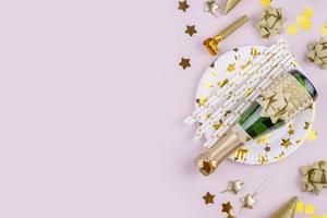 botella de champán y otros elementos de fiesta sobre fondo rosa foto
