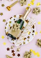 Champagne and decorations on pink background photo