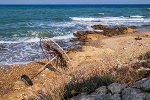 Sombrilla de playa abandonada en una playa rocosa frente al mar foto